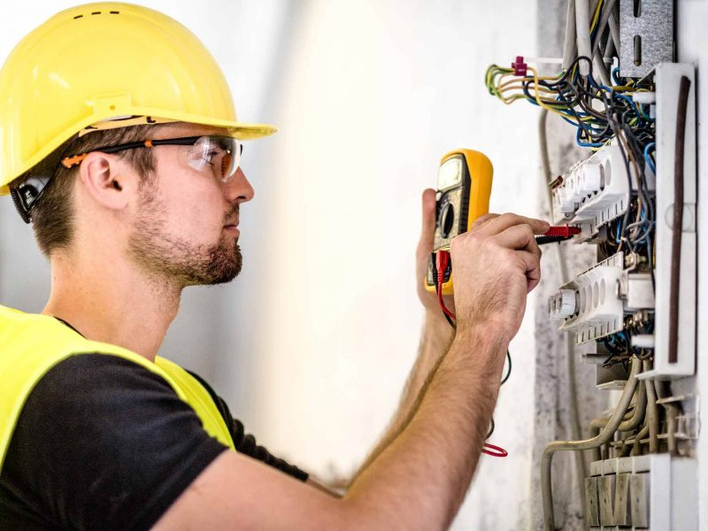 Man in hard hat testing an electrical system