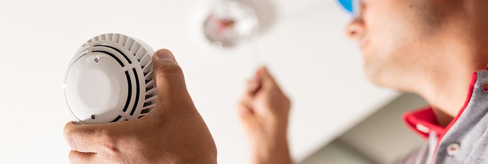 Man installing a smoke alarm on a ceiling