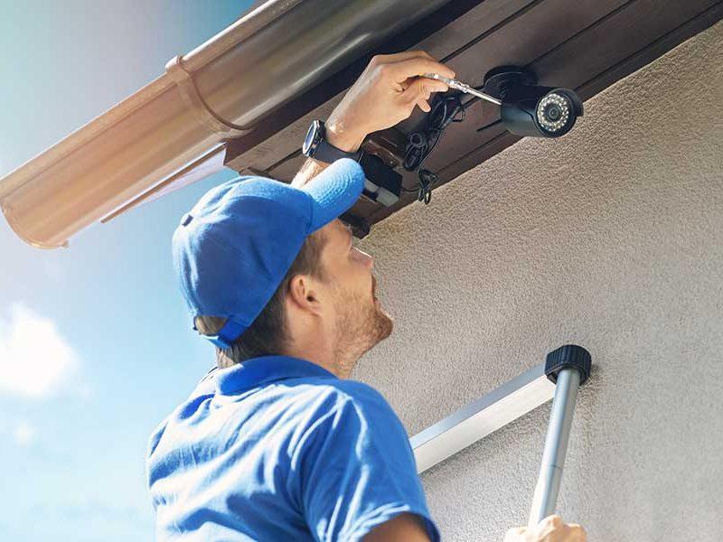 Man up a ladder installing a CCTV security camera